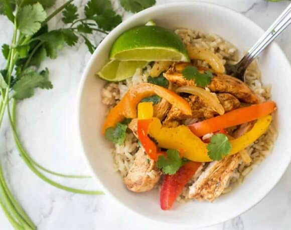 Chicken Fajitas and rice in a white bowl with a spoon and cilantro garnish