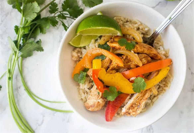 Chicken Fajitas and rice in a white bowl with a spoon and cilantro garnish