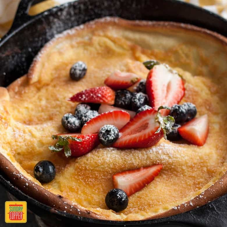 Berries and Cream Dutch Baby in a skillet with powdered sugar