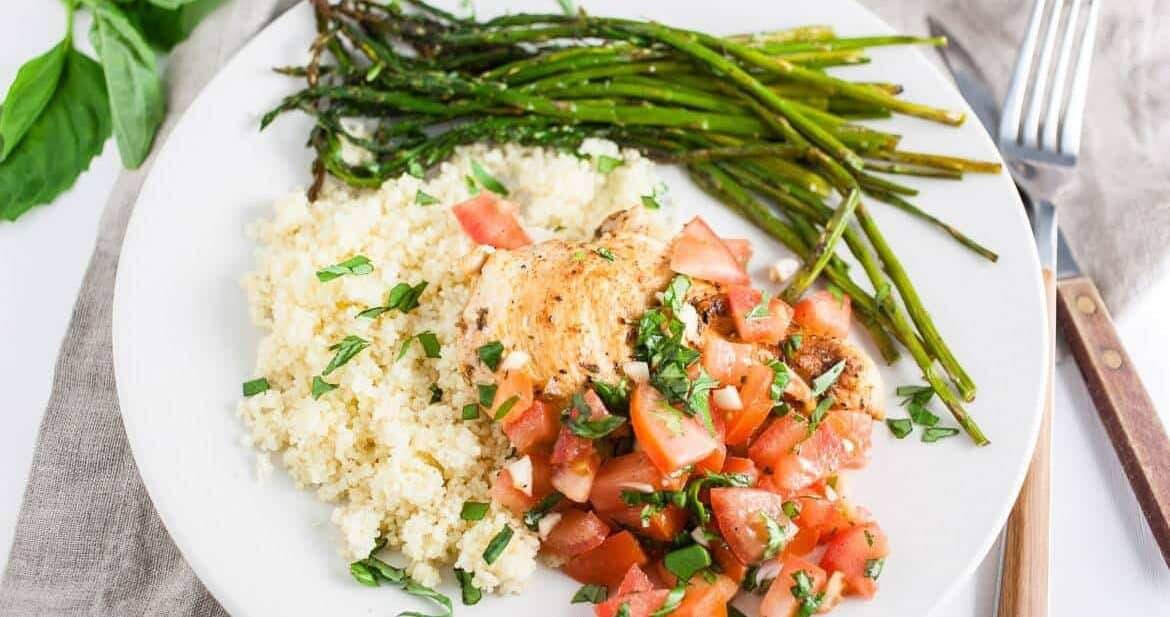 Grilled Bruschetta Chicken Breasts on white plate with asparagus and couscous