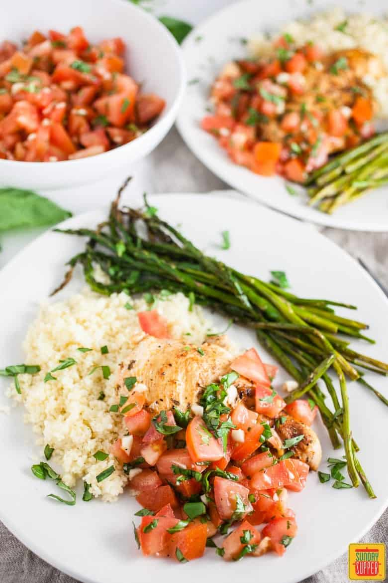 Grilled Bruschetta Chicken Breasts on a white plate with couscous and asparagus