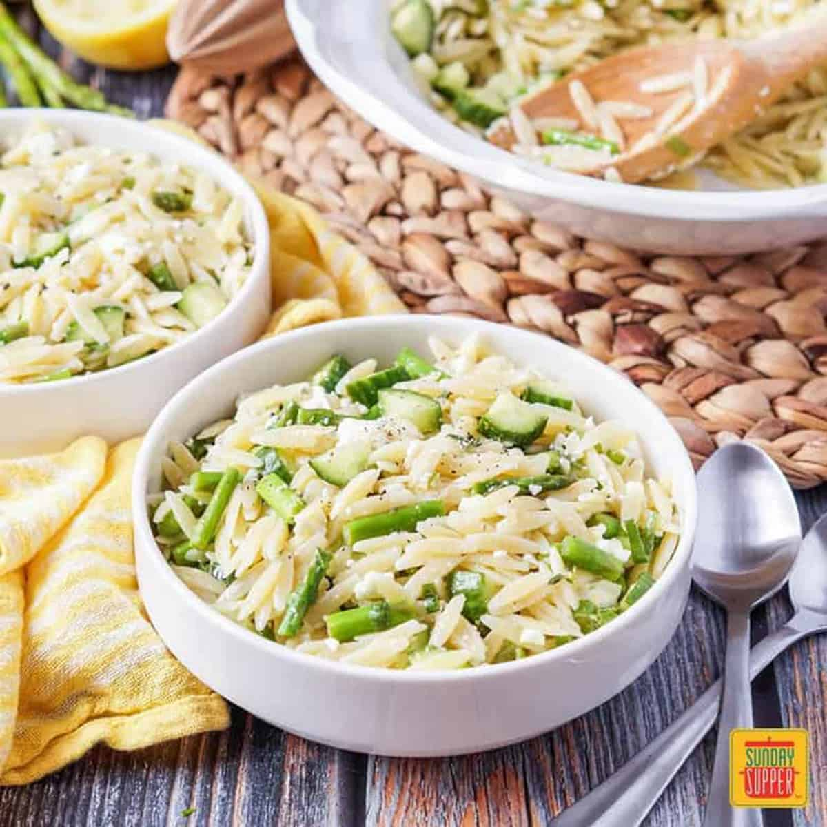 Lemon orzo pasta salad in two white bowls, with a third bowl visible in the background, with spoons on the side to eat