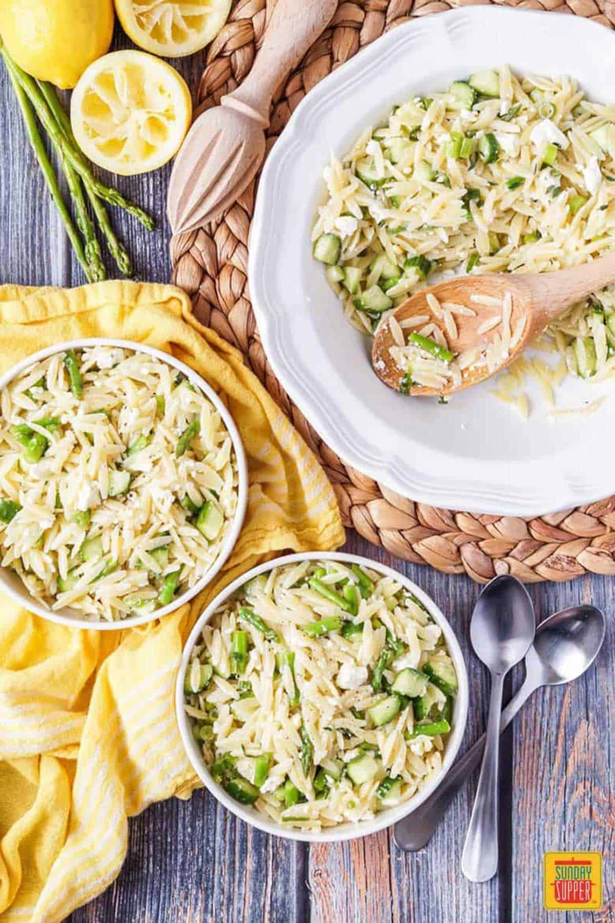 Two bowls of Lemon Orzo Pasta Salad next to a deep dish of pasta salad with a wooden serving spoon