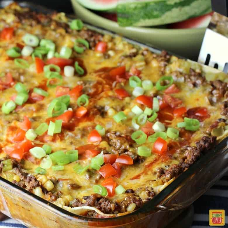 Mexican lasagna with corn tortillas in a glass casserole dish for best ground beef recipes