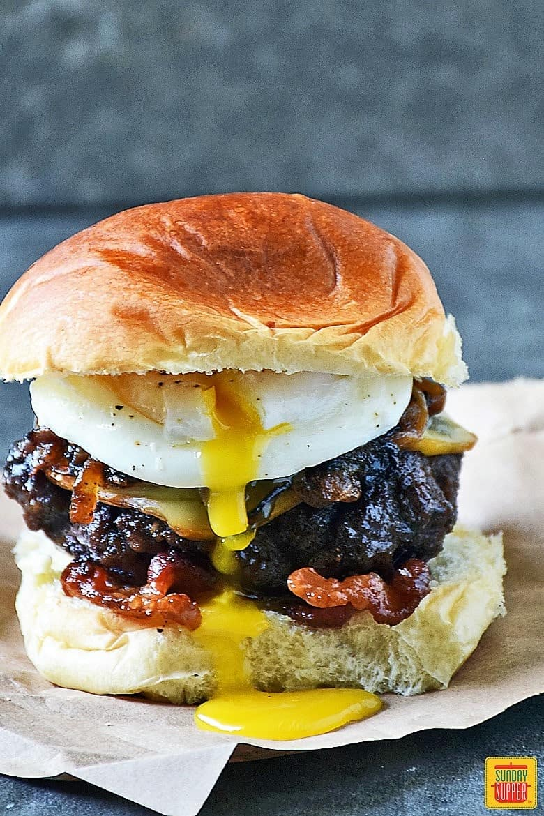 Grilled Burger Topped With Caramelized Onions Gruyere Cheese And A Poached Egg