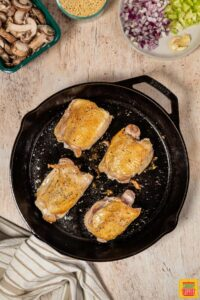 cooking chicken in a black skillet
