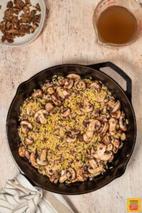 orzo and mushrooms in a black skillet