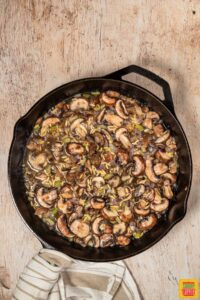 orzo and mushrooms cooking in liquid in a black skillet