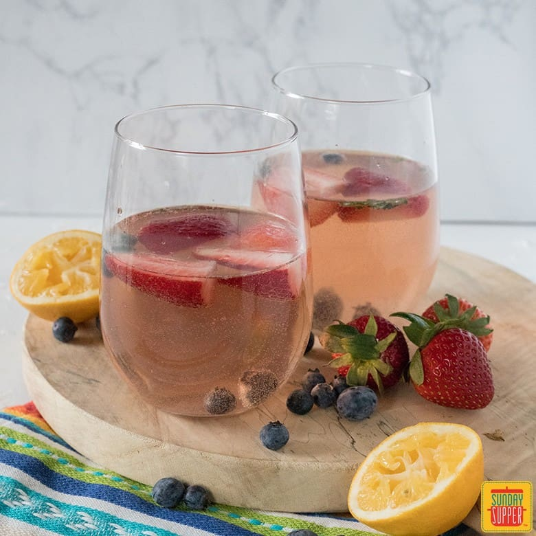 two glasses of rose sangria on a rustic round board