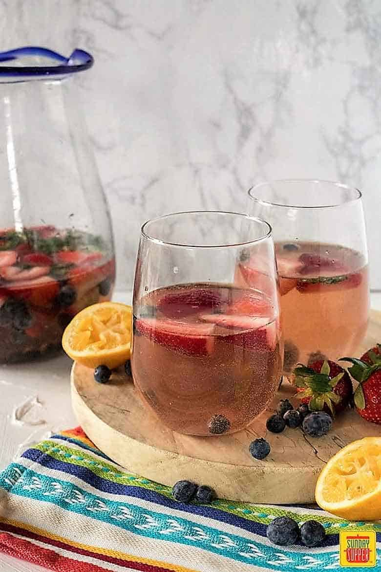 two glasses of rose sangria on rustic wooden board in front of pitcher