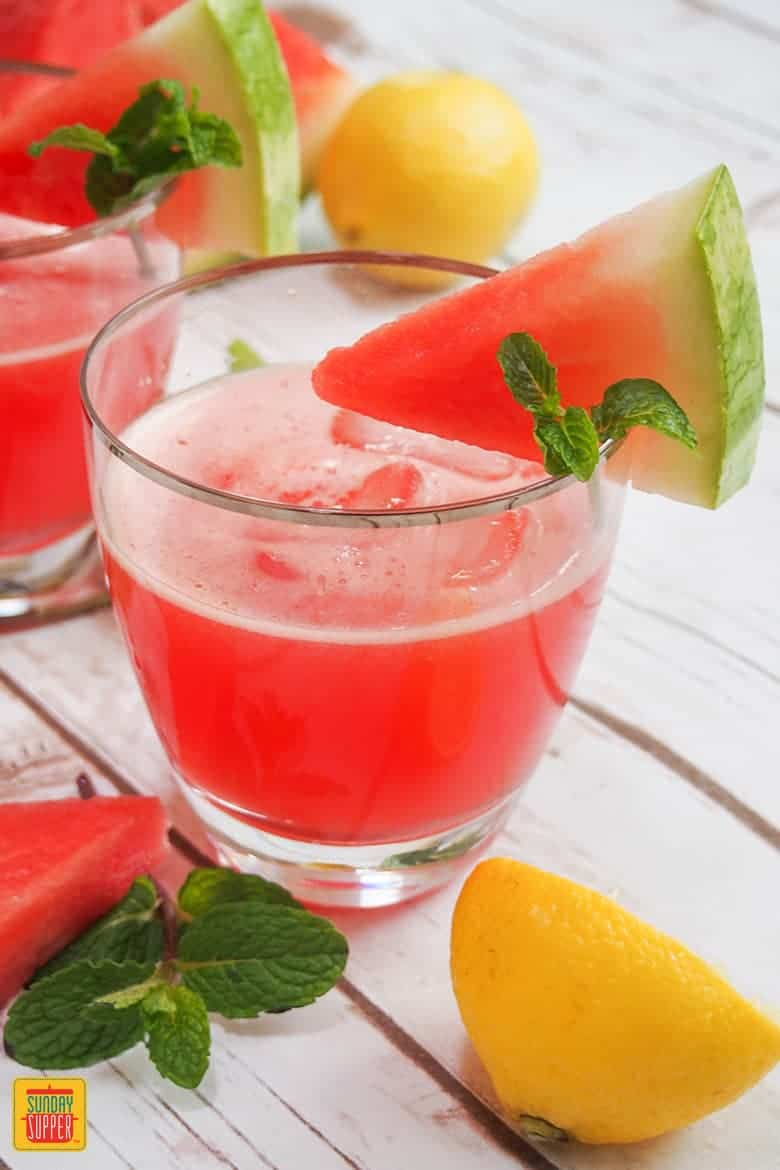 watermelon lemonade in a glass with a watermelon slice on the rim of the glass