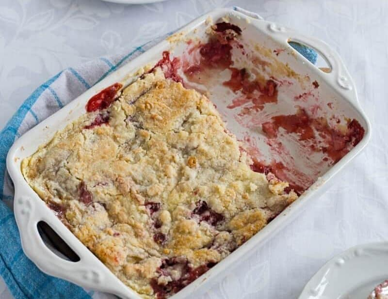 Strawberry Banana Dump Cake in a baking dish on a table, served in plates. Delicious and easy fruit dessert