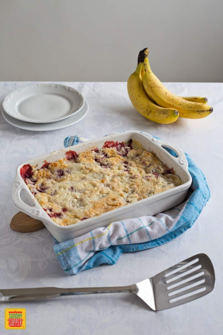 Strawberry Dump Cake in a pan on a table. A delicious fruit dessert everyone can make .