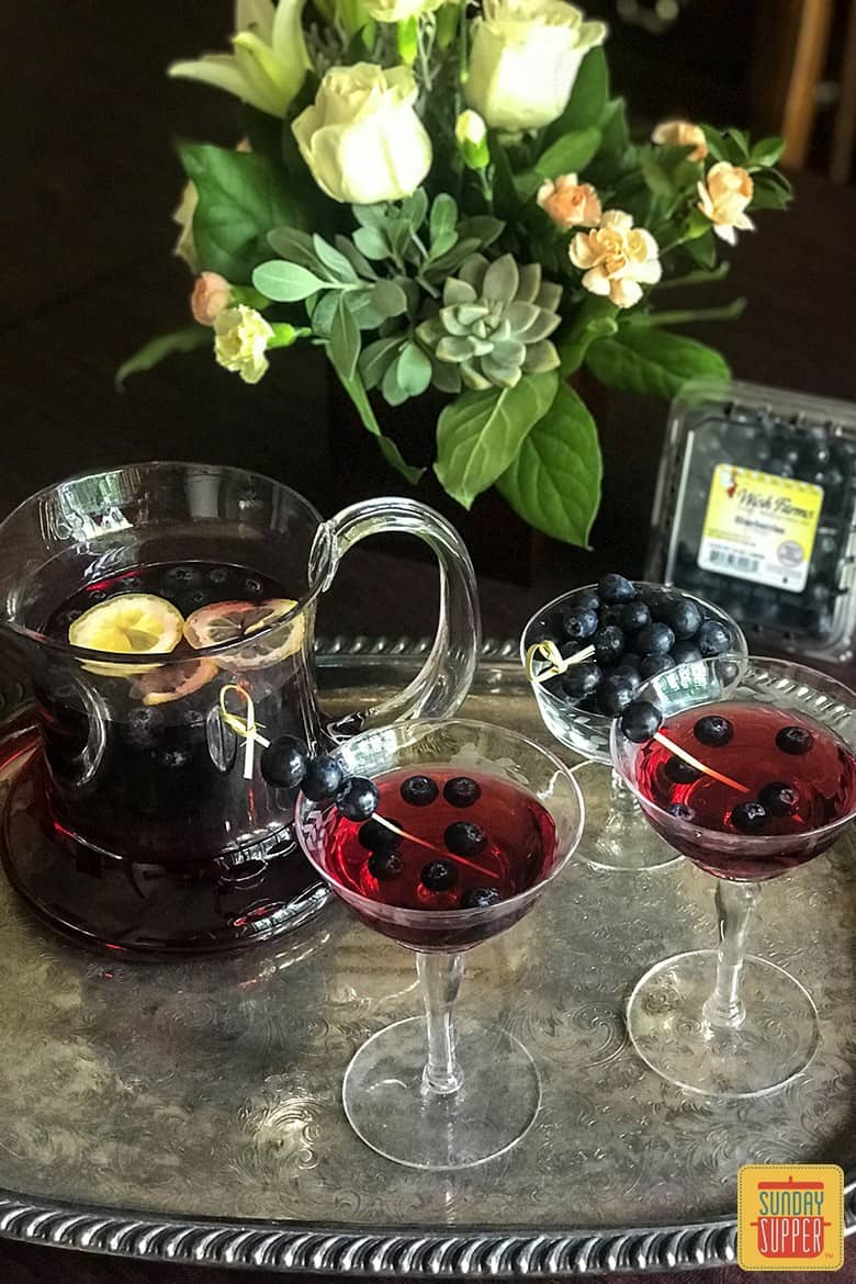 Blueberry Sangria in two glasses with fresh blueberries in front of a pitcher of blueberry sangria