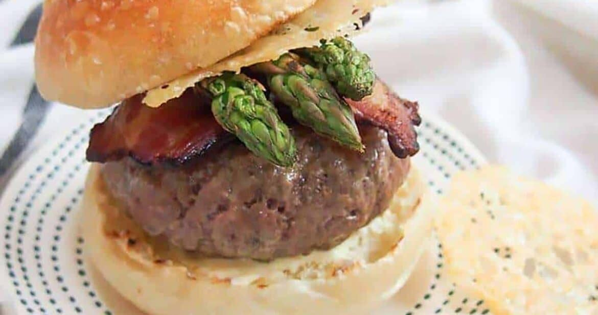 A loaded burger with asparagus spears and bacon on a bun with Parmesan crisps