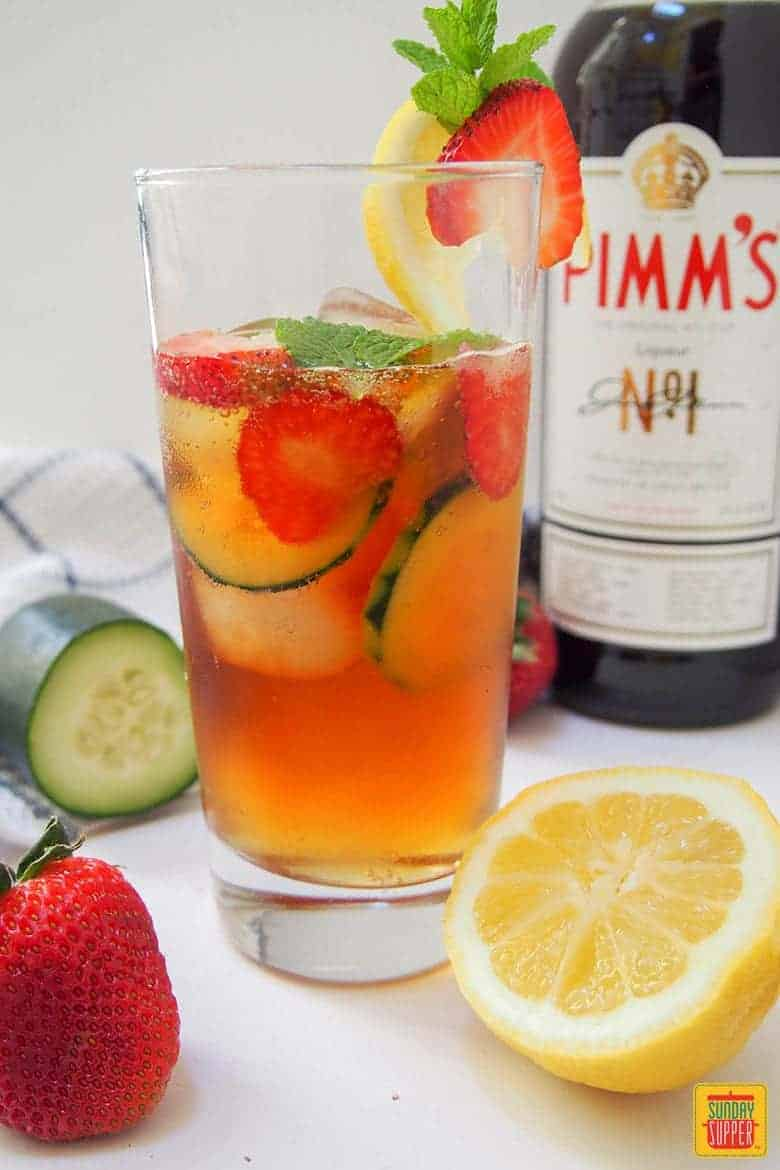 Pimm's Cup Cocktail with fresh strawberry and lemon and a bottle of Pimm's in the background