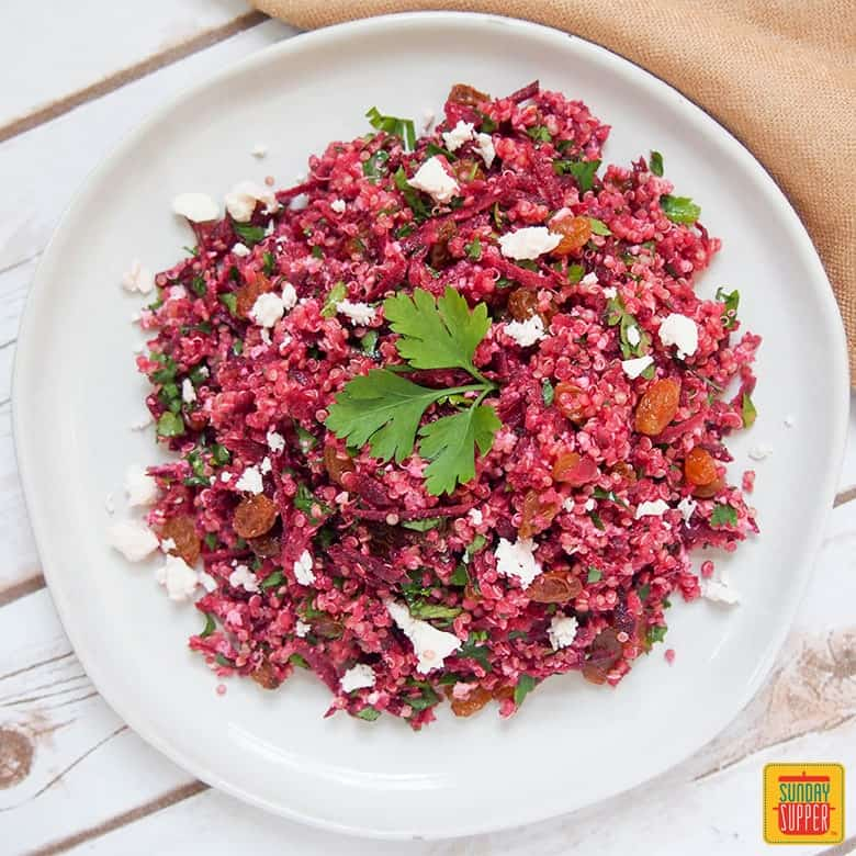 raw beet quinoa salad on a white plate garnished with fresh parsley leaves