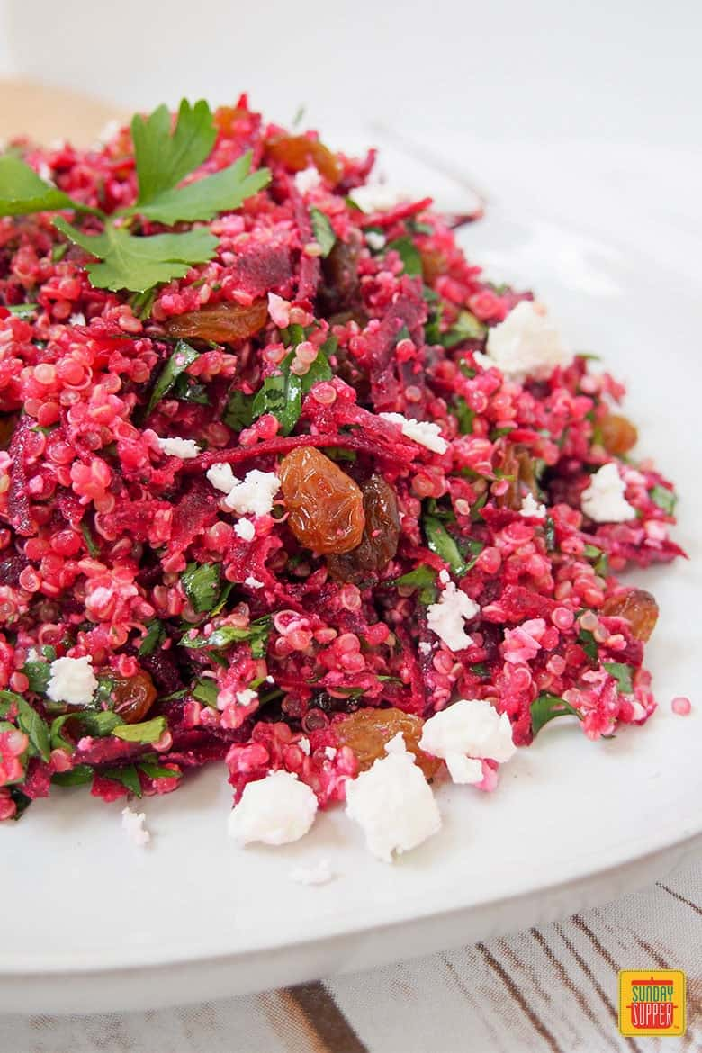 raw beet quinoa salad on a white plate ready to eat