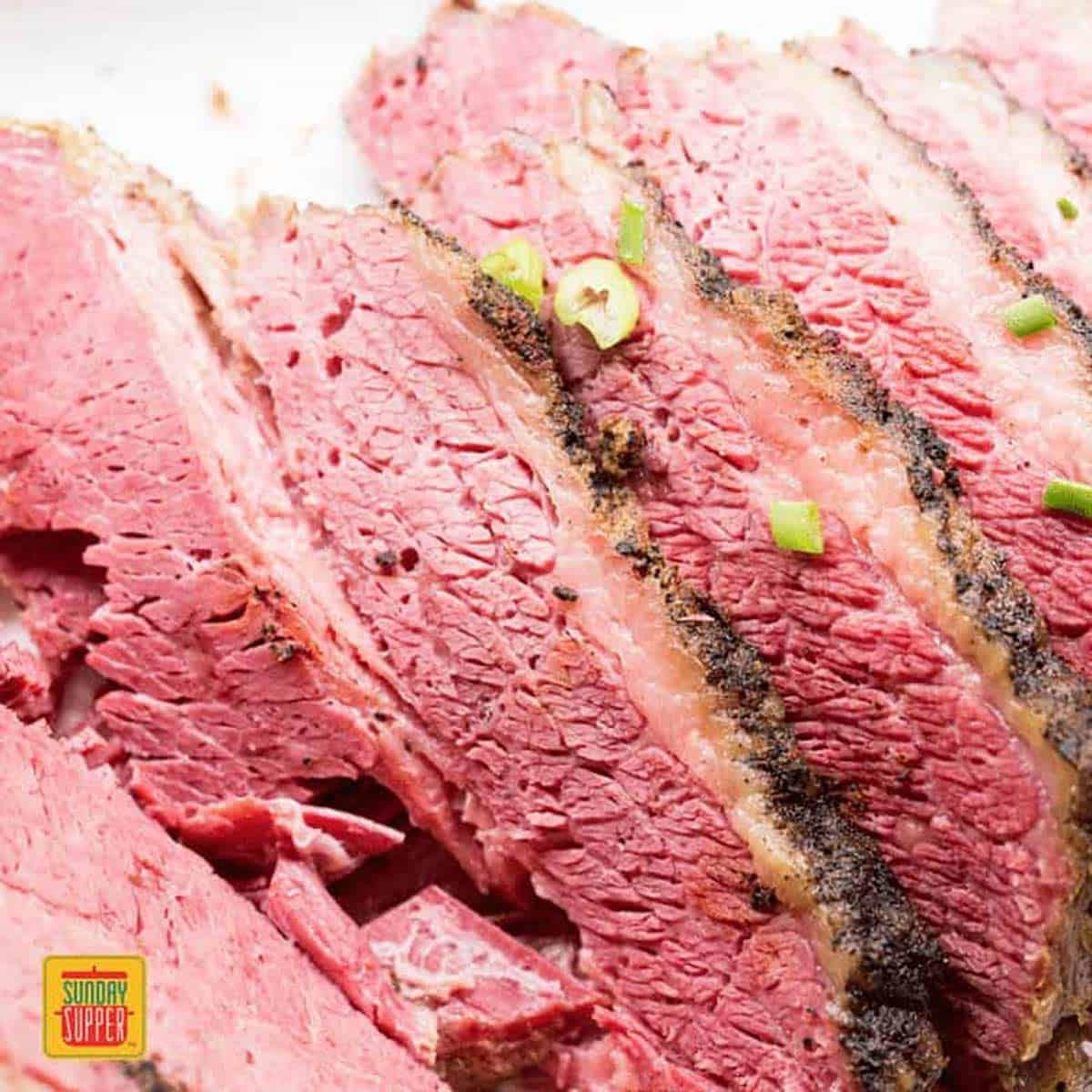 Slices of slow cooker brisket with green onions