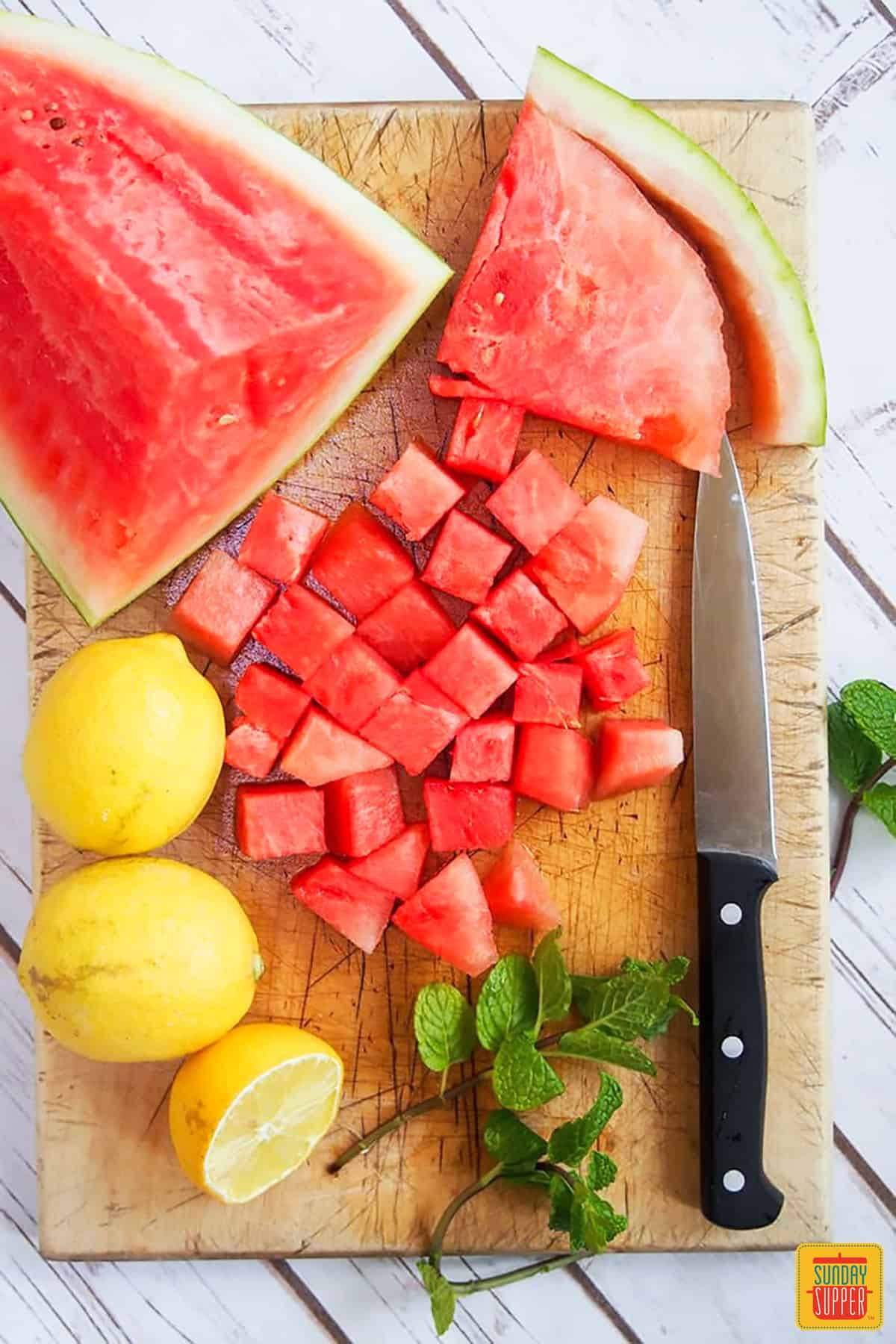 Ingredients for homemade lemonade on a cutting board with a paring knife