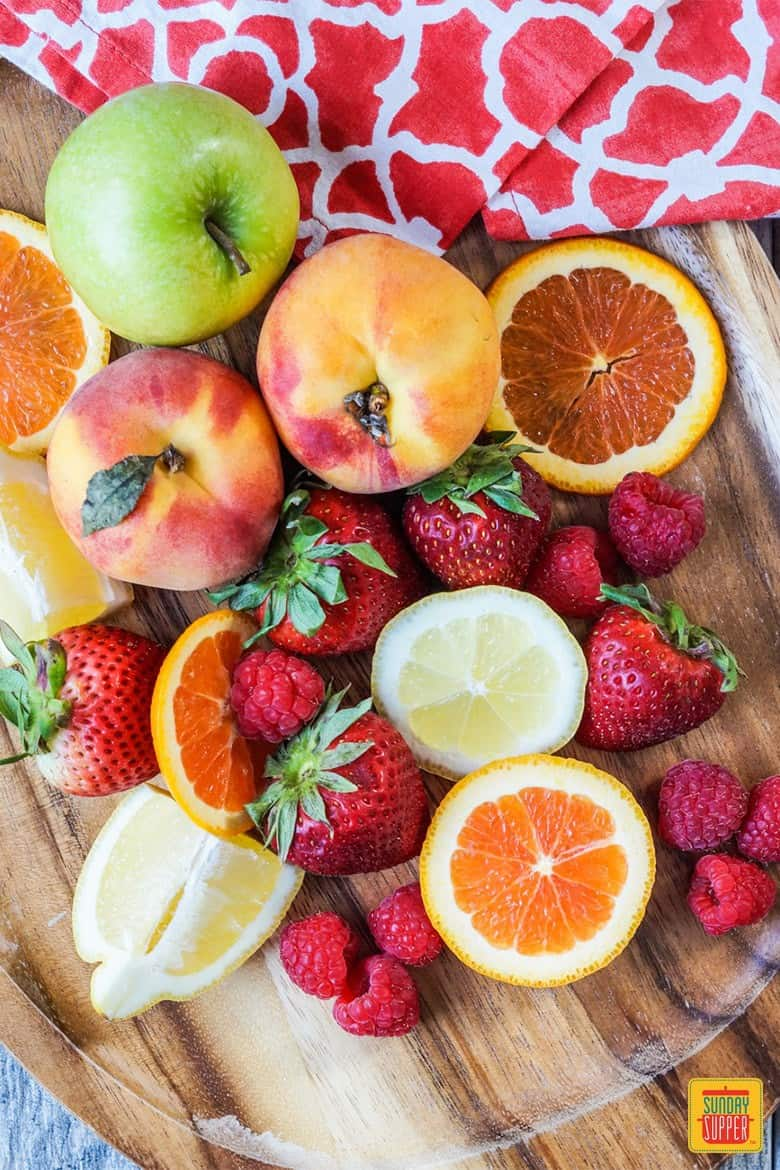 Fresh fruit on a cutting board: peaches, apples, orange slices, strawberries, and lemons