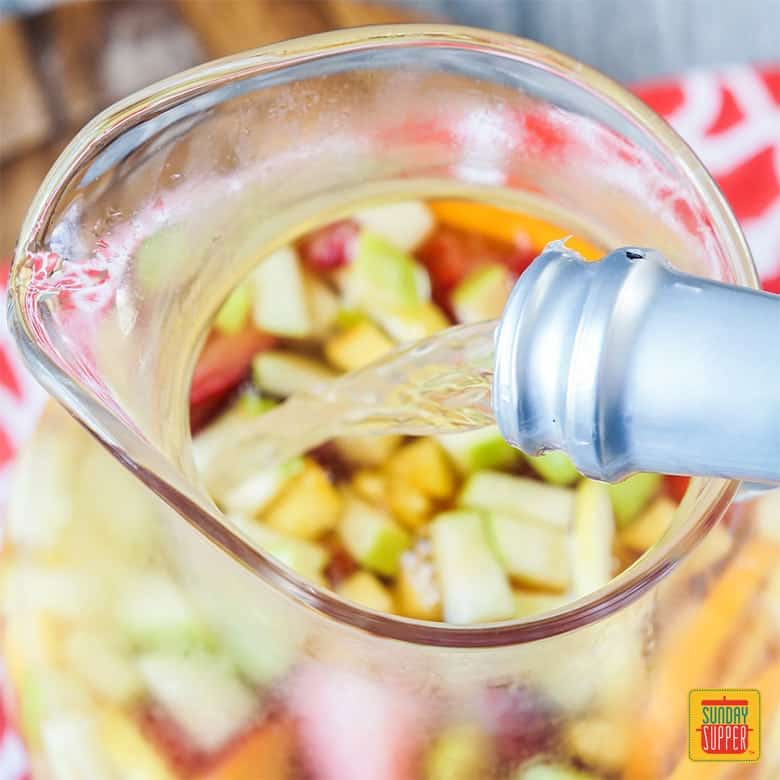 Moscato being poured into a pitcher with fresh fruit slices
