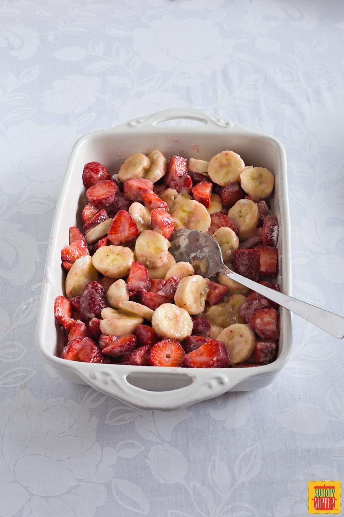 Strawberries and bananas in a white rectangular baking dish mixed with cornstarch and sugar