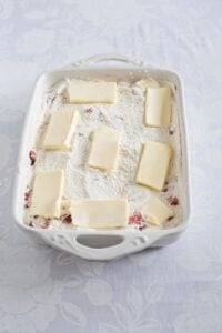 Slices of butter arranged over the dump cake in the baking pan