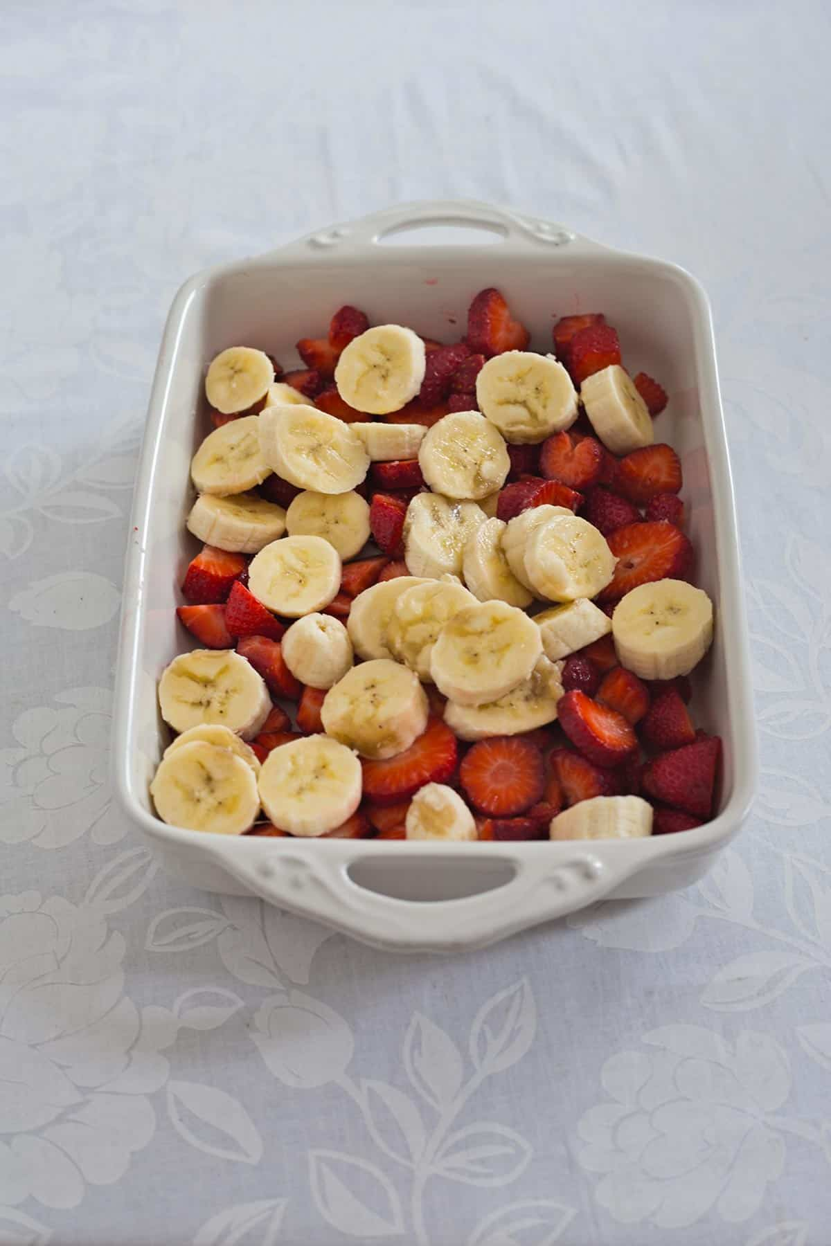 Strawberries and bananas in a white rectangular baking dish to make strawberry dump cake with bananas