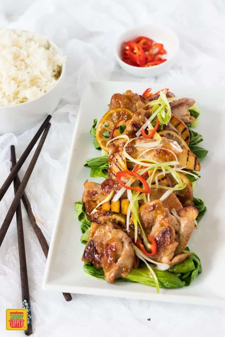 Asian Peach Glazed Chicken with chopsticks on a white serving platter with a side of rice