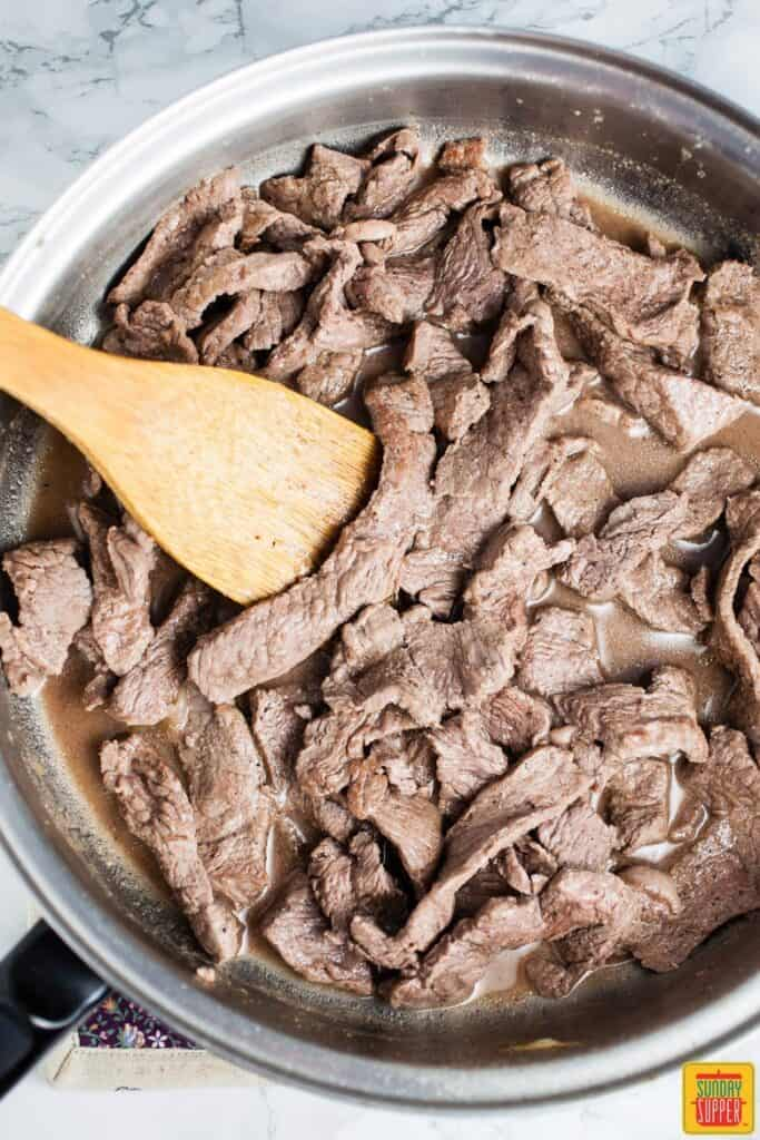 Cooking the steak for cheesesteak sliders