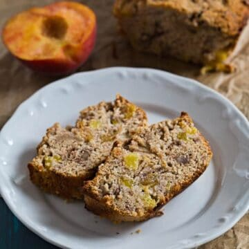 Two slices of Healthier Peach Bread on a plate with peaches and the loaf on the side
