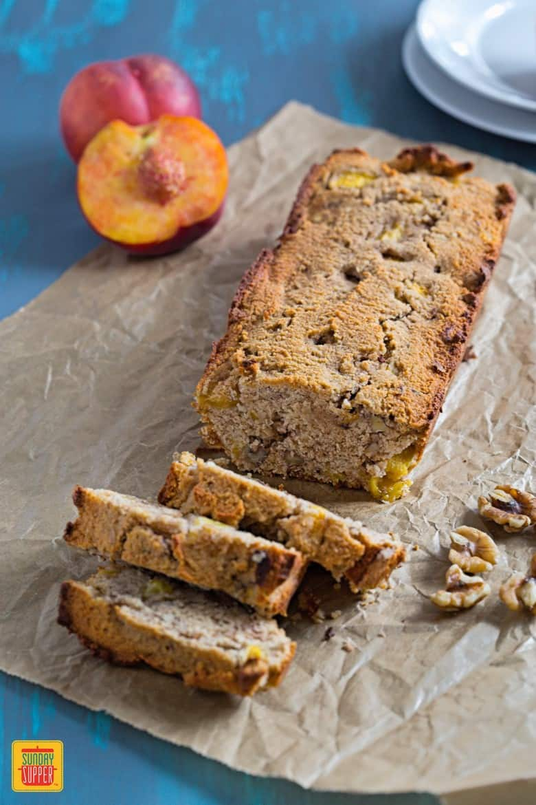 Peach Bread cut on a blue wooden table with peaches and walnuts on the side