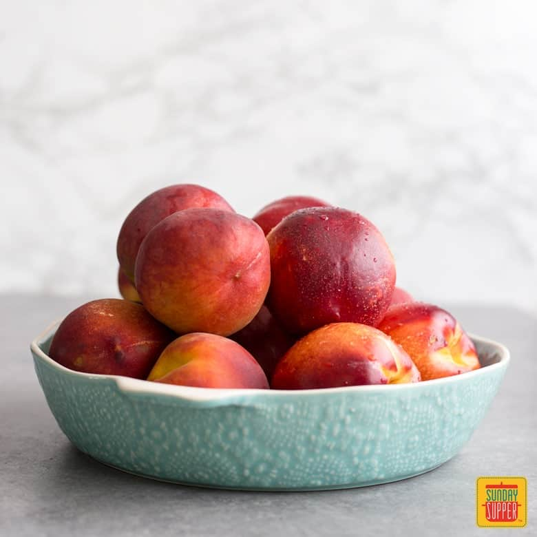A light teal lacy bowl of peaches and nectarines