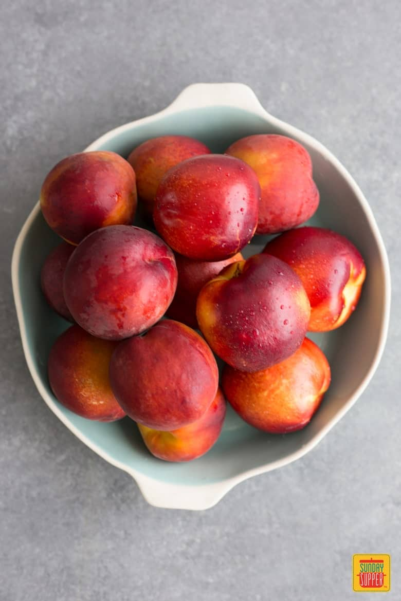 A white bowl with handles full of peaches and nectarines