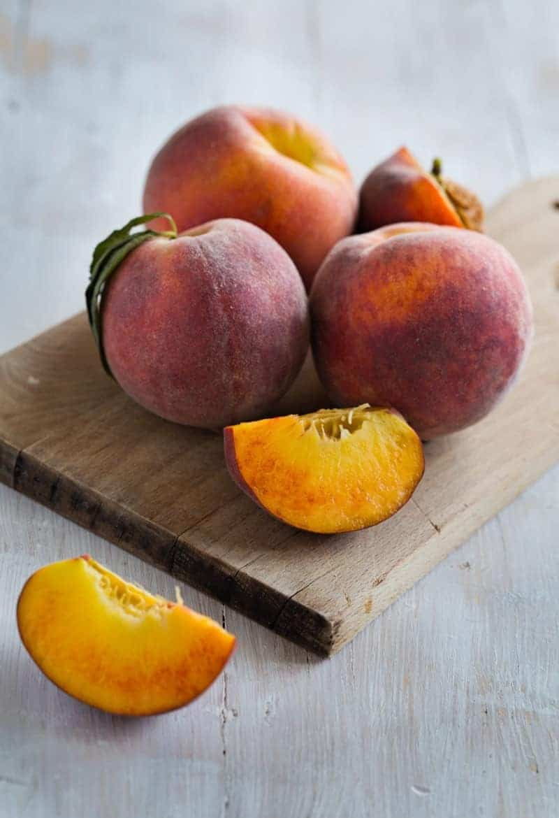 Delicious and juicy peaches on a wooden background