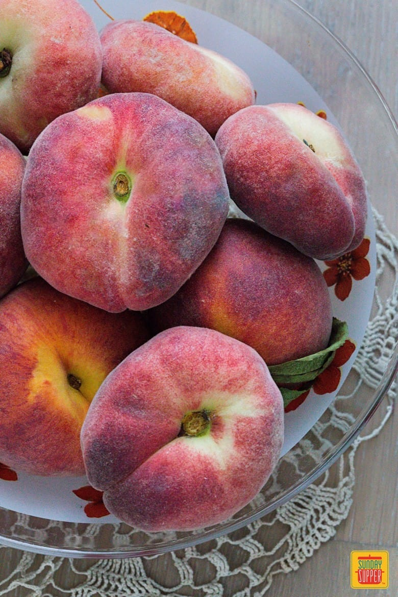 Different kinds of peaches in a glass fruit bowl