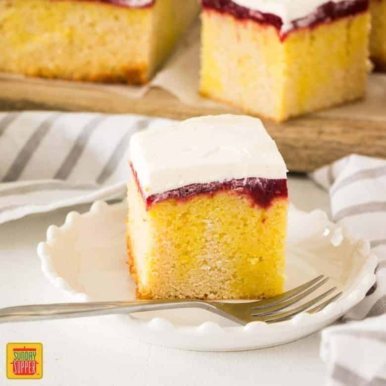 Raspberry Lemon Jello Poke Cake square served in a white dish with a fork