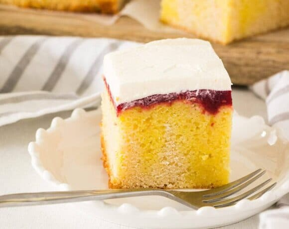 Raspberry Lemon Jello Poke Cake is a combination of soft vanilla cake soaked in lemon jello then topped with an easy homemade raspberry jam and whipped cream.