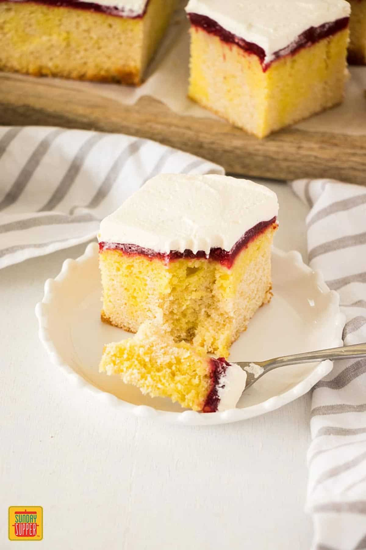 Lemon jello poke cake on a white plate with a slice taken out and a fork on the plate