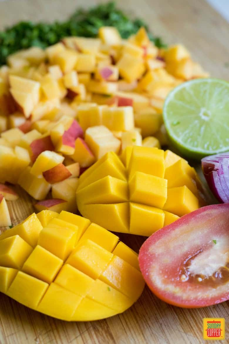peach mango salsa ingredients cut up on a wooden board