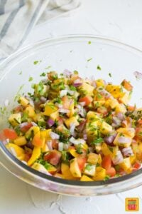 peach mango salsa ingredients mixed up in a clear bowl ready for serving