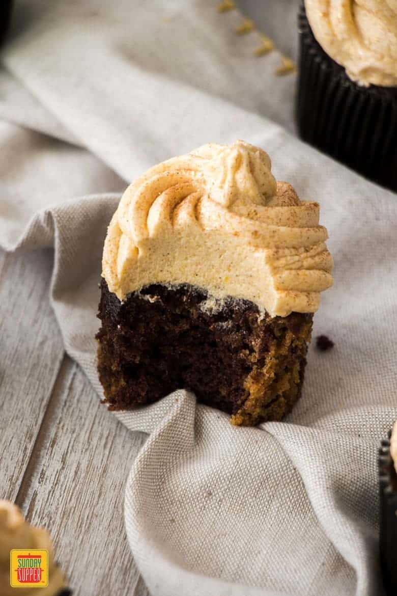 Pumpkin Cupcake Recipe with Spiced Pumpkin Frosting and a bite taken out of it