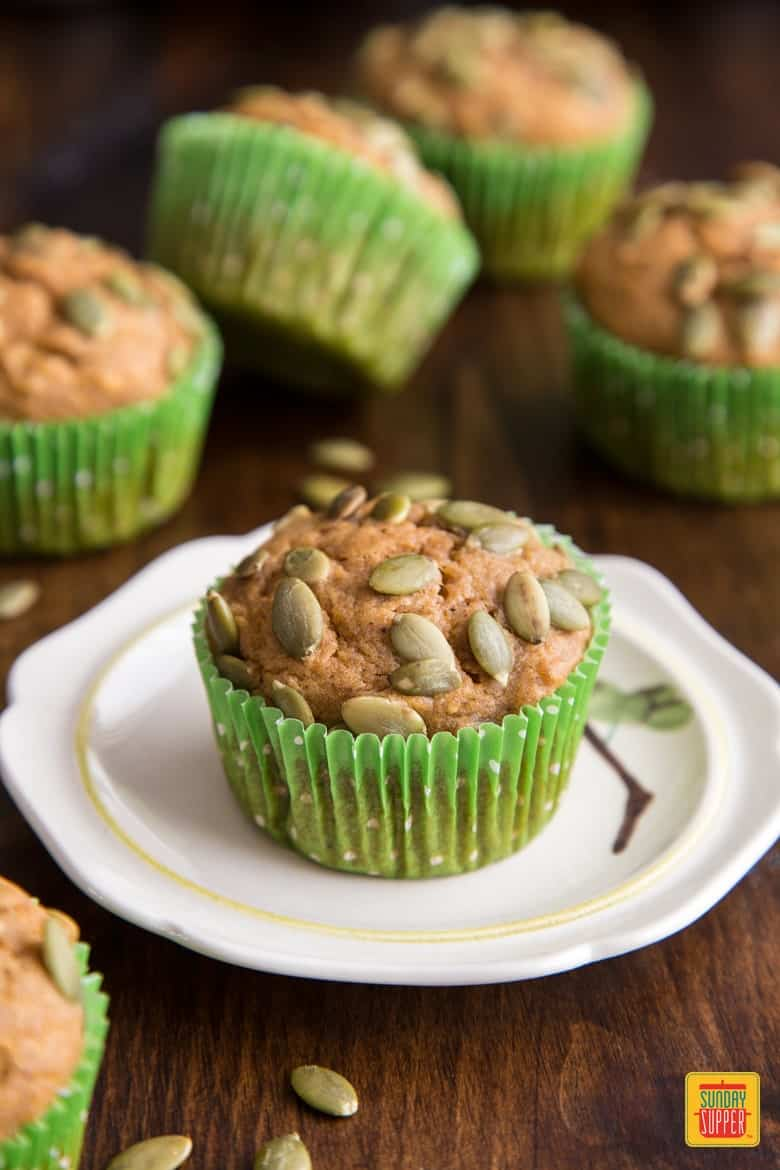 A pumpkin muffin topped with pumpkin seeds on a white plate