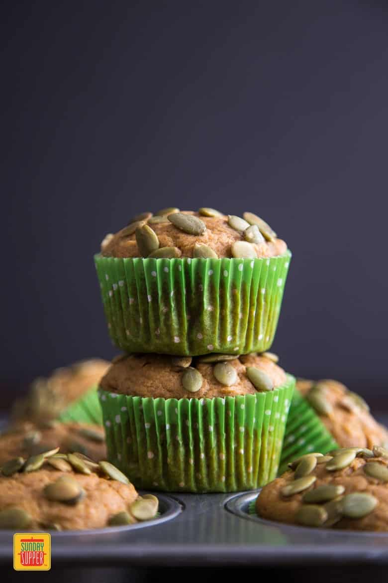 2 easy pumpkin muffins stacked on top of muffin tray