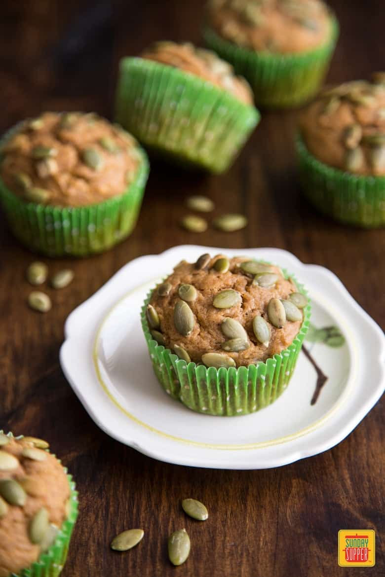 Easy Pumpkin Muffin Recipe on a white plate next to more pumpkin muffins