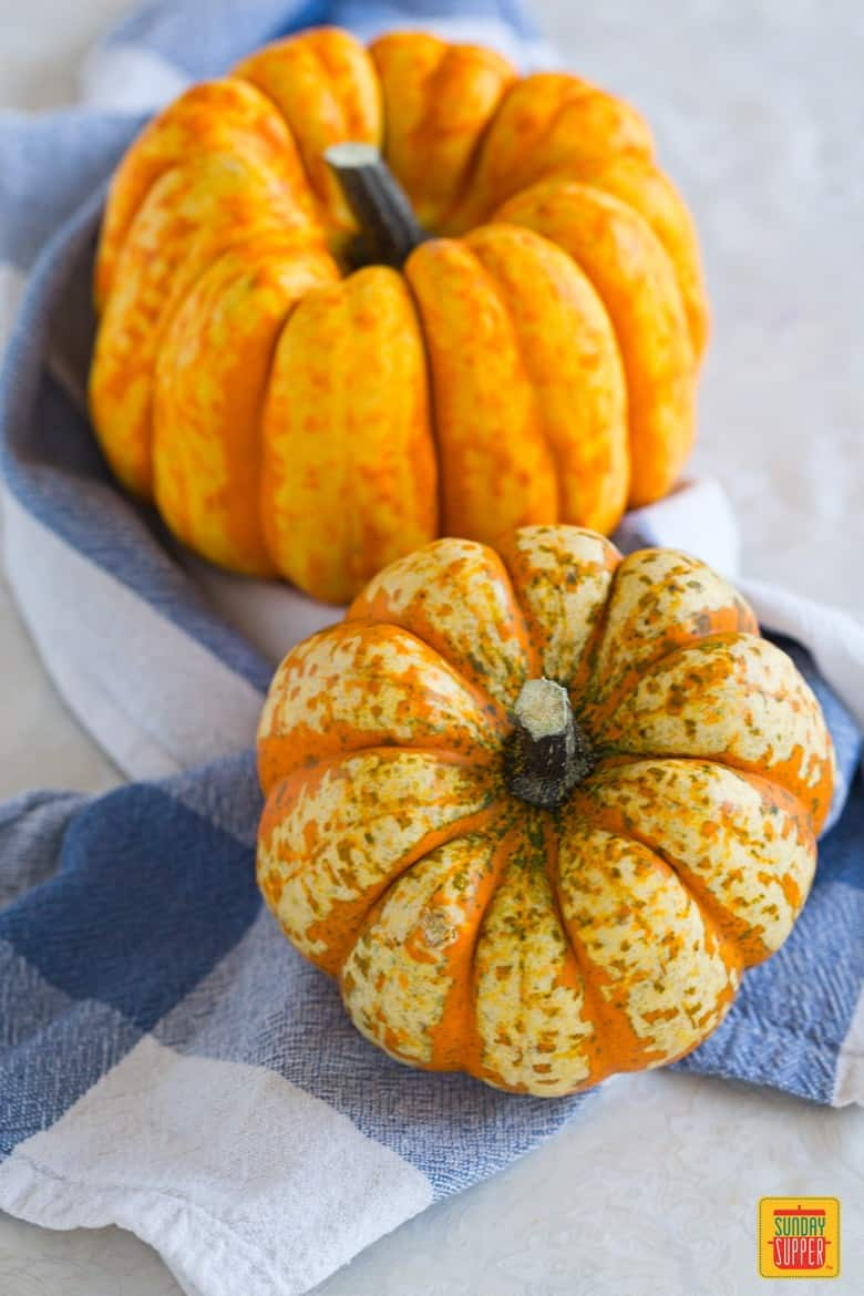 two pumpkins on a blue and white tea towel; pumpkin health benefits