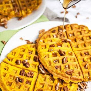 Pouring syrup onto two pumpkin waffles on a white plate