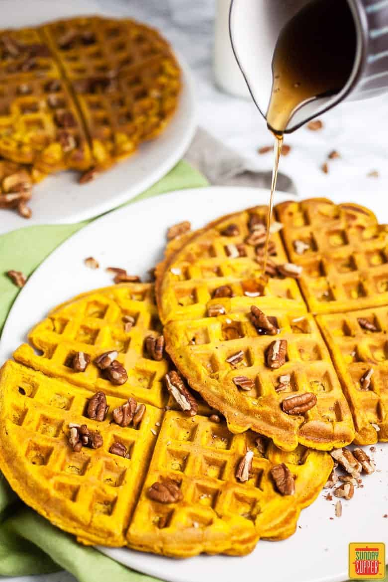 Pumpkin Waffle Recipe served on a white plate with pecans and a drizzle of maple syrup being poured on top