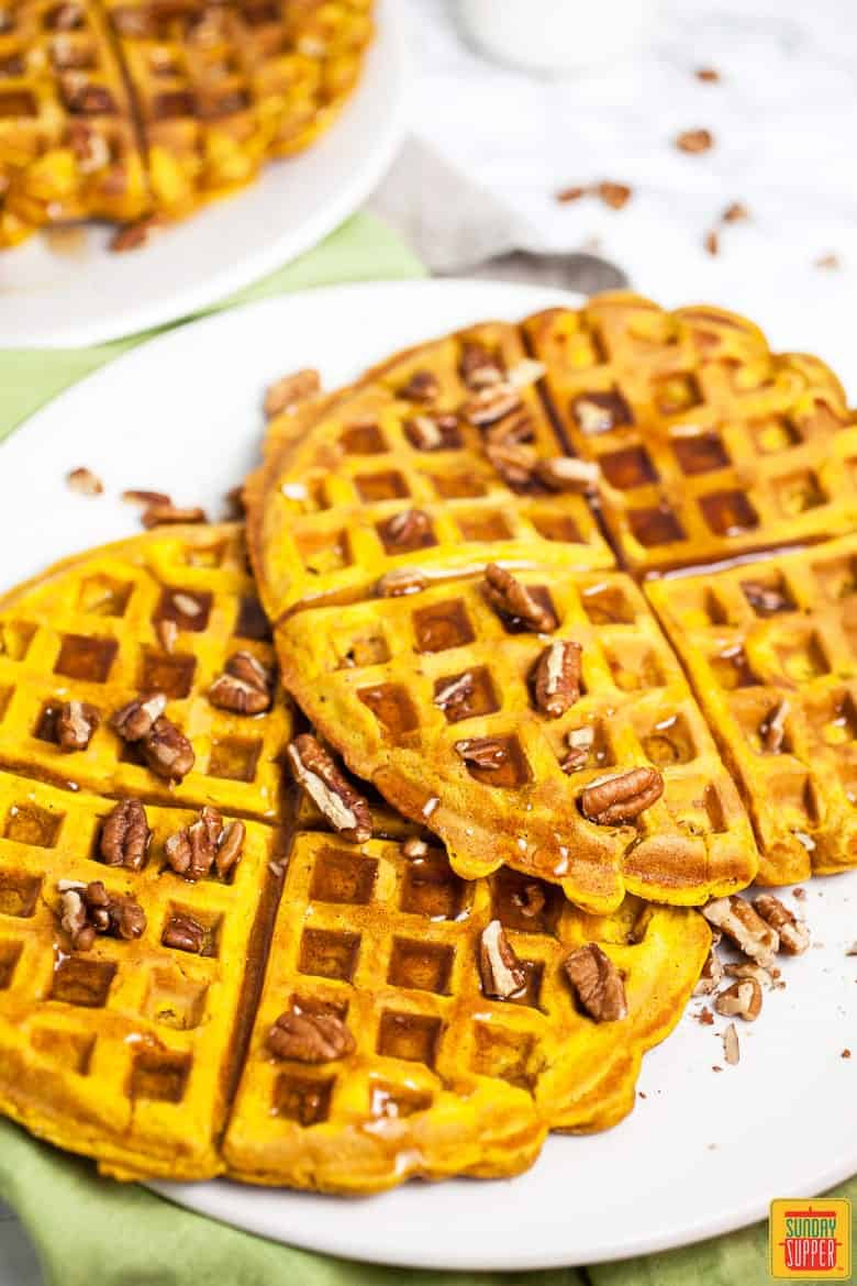 Two pumpkin waffles on a white plate with pecans on top and syrup